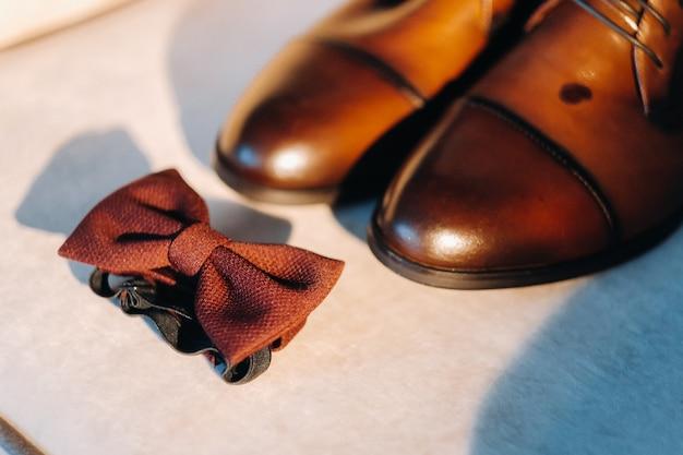 Коричневый галстук-бабочка на светлом фоне и сапоги.