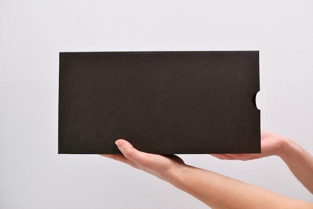 白い背景の分離に手に茶色のボックス。手にテキスト用のスペースがある段ボール箱。