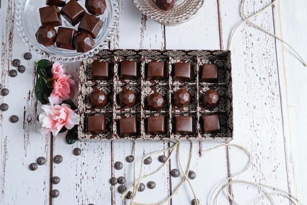 Коричневая коробка шоколадных конфет, рядом с цветами, шоколадными каллетами и веревками.