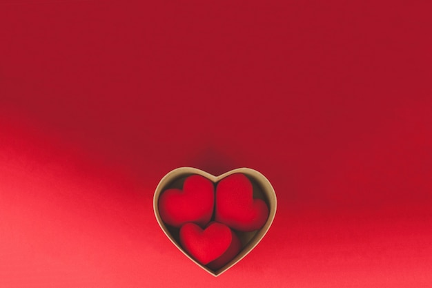 Brown box with hearts inside on a red table