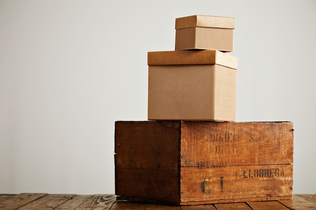 Коричневые коробки разных размеров и текстур, расположенные в виде пирамиды на деревенском деревянном столе, изолированном на белом