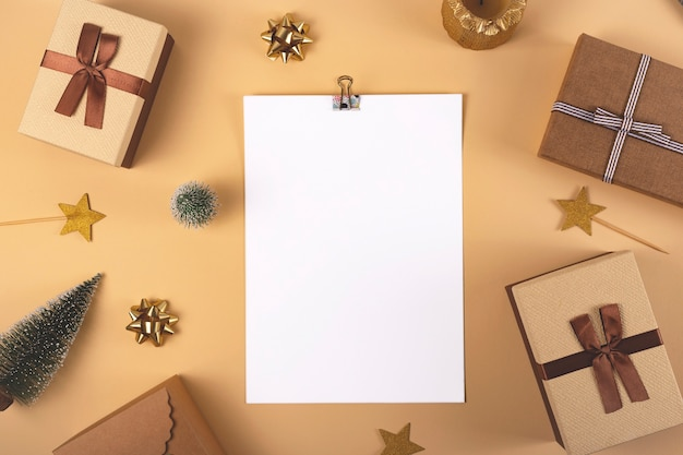 장식 및 종이의 흰색 빈 시트와 중립 배경에 리본 크리스마스 선물 갈색 상자 상위 뷰 평면 누워 복사 공간을 모의