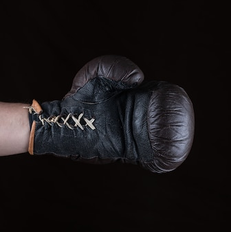 Brown boxing glove dressed on man's hand