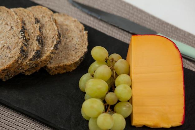 Черный хлеб, виноград и сыр гауда на грифельной доске