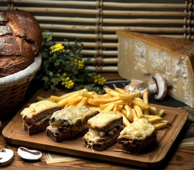 Brown bread sandwich with grated cheese and french fries