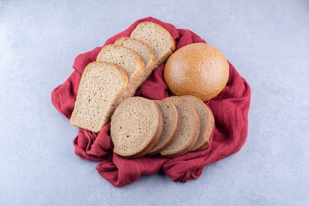 Ломтики черного хлеба и булочка на куске ткани на мраморной поверхности