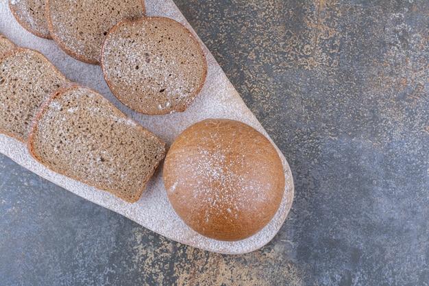 Ломтики черного хлеба сложены на деревянной доске на мраморной поверхности