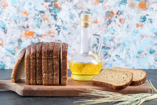 Fette di pane integrale e bottiglia di olio su tavola di legno.