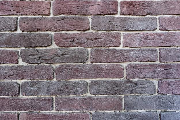 茶色のレンガの壁。白い詰物が付いている古い暗い茶色と赤レンガのテクスチャ