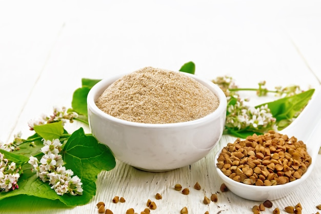 Brown buckwheat flour in a bowl, brown groats in a spoon, buckwheat flowers and leaves on white wooden board background