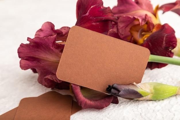 흰색 콘크리트 바탕에 아이리스 버건디 보라색 꽃이 있는 갈색 명함. 측면보기