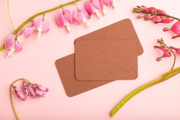 분홍색 디센트라가 있는 갈색 명함, 분홍색 파스텔 배경에 깨진 하트 꽃. 평면도