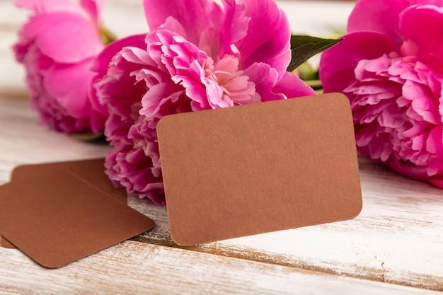 흰색 나무 바탕에 분홍색 모란 꽃이 있는 갈색 명함. 측면보기, 복사 공간,