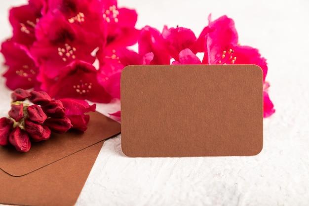 灰色のコンクリートの背景に紫のツツジの花と茶色の名刺。側面図、コピースペース
