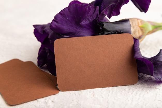 Коричневая визитная карточка с фиолетовыми цветами ириса на белом фоне бетона. вид сбоку, копировать пространство