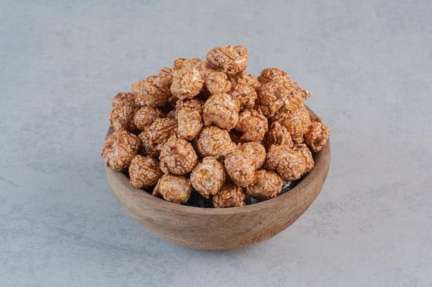 Коричневый попкорн, покрытый конфетами, в миске на мраморной поверхности