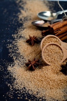 Brown cane sugar, cinnamon sticks and star anise closeup on black board background.
