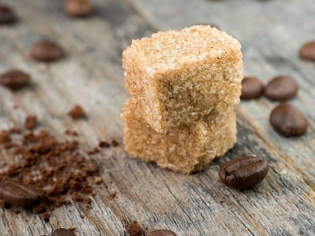 소박한 나무 배경에 원두 커피와 갈색 지팡이 설탕.