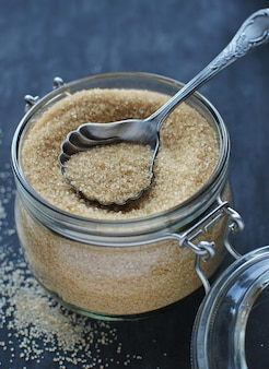 Brown cane sugar with vintage spoon in glass jar.