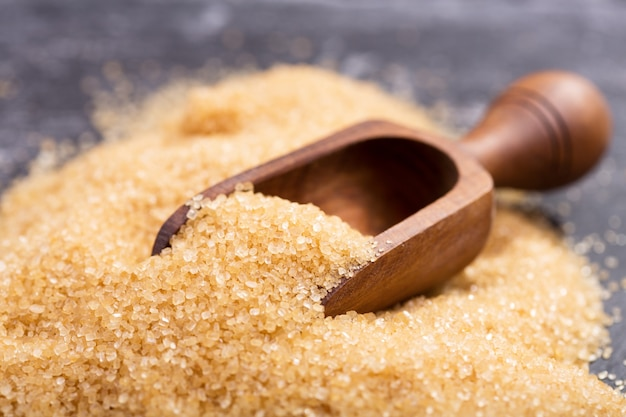 Brown cane sugar in a wooden scoop on dark table