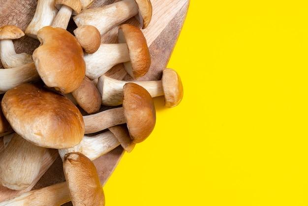 Коричневая крышка boletus edulis на разделочной доске на желтом фоне. съедобные грибы на деревянной доске на кухне. никто