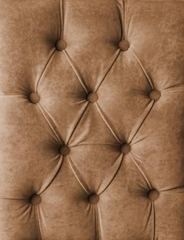 茶色のカピトン市松模様の柔らかい生地のテキスタイルコーチはボタンで装飾をベロアします