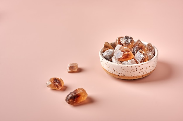 Brown caramelized lump cane sugar cubes in a bowl on pink powdered background selective focus copy