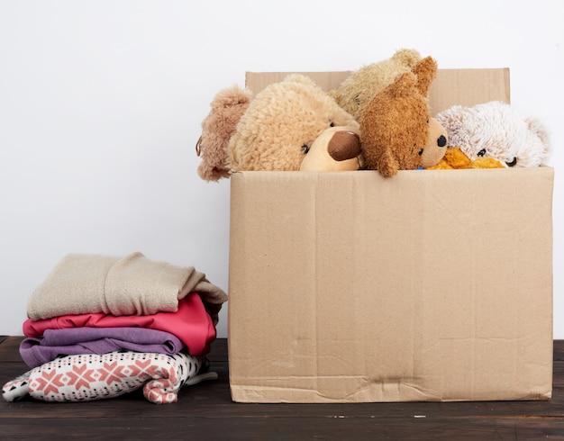 Коричневая картонная коробка с вещами и детскими игрушками