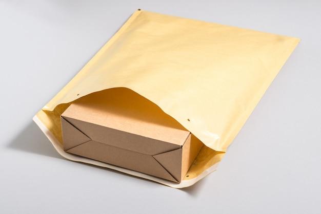 大きな郵便封筒の中の茶色の段ボール箱