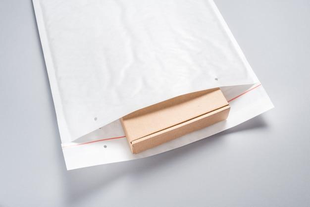 灰色の背景に白いバブルの封筒に詰められた茶色の段ボール箱