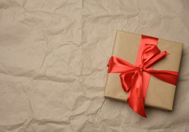 Brown cardboard box tied with a silk red ribbon on a brown paper background, top view, close up