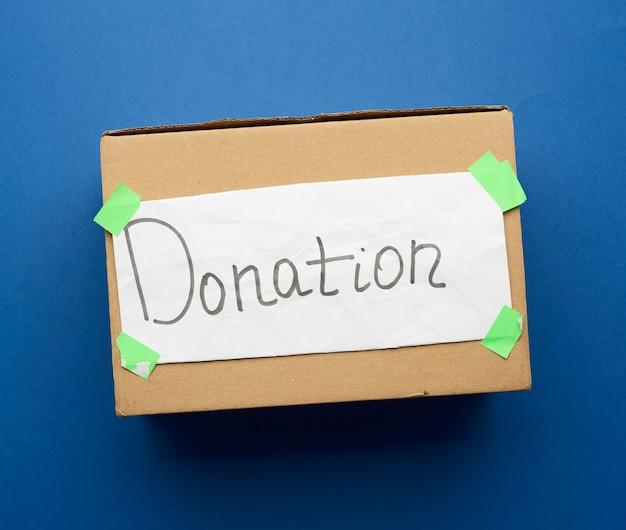 白いシーツを貼り付けた茶色の段ボール箱と碑文の寄付