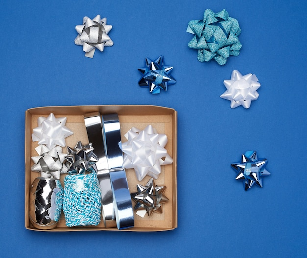 Brown cardboard box with a set of decor ribbons and bows for wrapping gifts