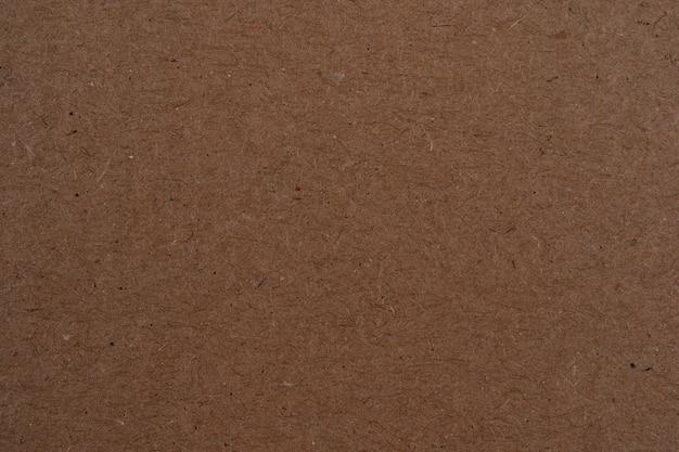 茶色の段ボールシート紙の背景茶色の色の紙は、表面に穀物の詳細を示しています Premium写真
