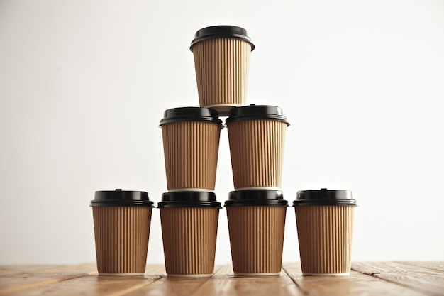 Brown cardboard take away paper cups with black caps in pyramid house shape on rustic vintage table in center of picture