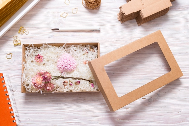 Brown carton box with crinkle cut paper shred filler  on wood table