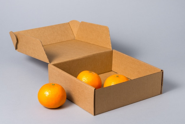 Brown carton cake box with cover with fruits, on grey background