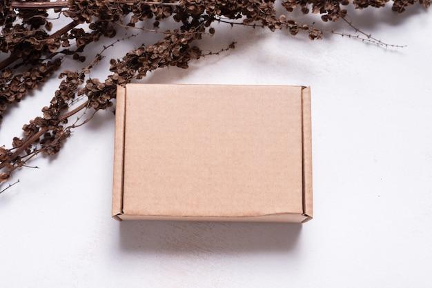 乾燥した枝のモックアップで飾られた茶色のカートン段ボール箱