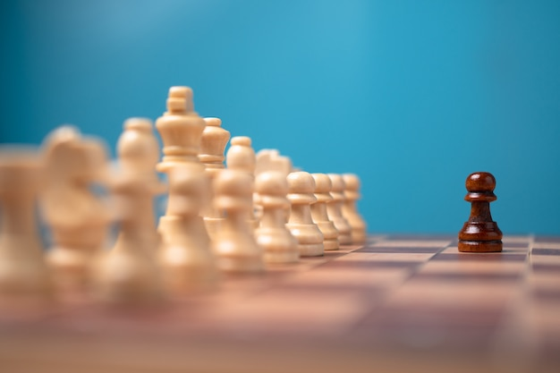 Brown chessman standing in front of white chess, concept of challenge in the competition