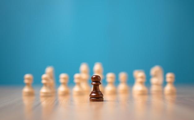 白いチェスの前に立っている茶色のチェスマン、競争の挑戦の概念