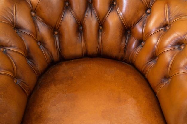 ブラウンチェスターフィールドスタイルの革張りのアームチェアは、モダンなデザインをクローズアップ