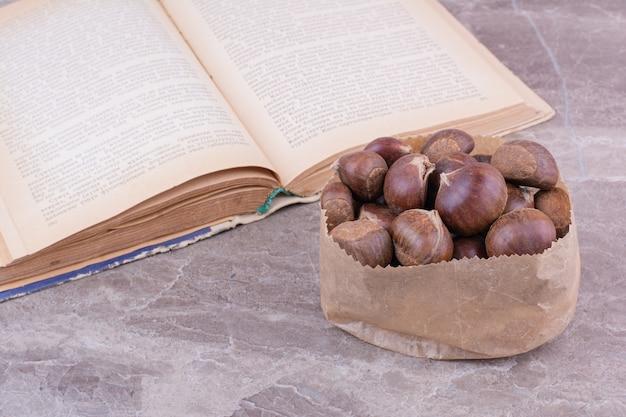 石の上の紙かごの中の茶色の栗