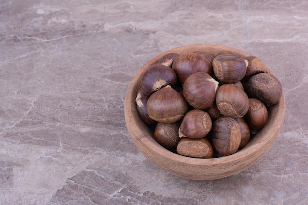 Castagne marroni in una tazza di legno sulla pietra