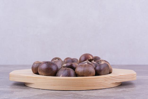 Castagne marroni in un vassoio di legno su marmo.