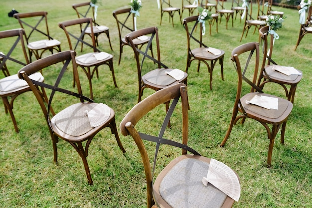 Brown chiavari chairs and hand fans outdoors on the grass