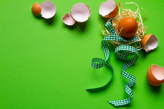 Brown chicken egg in a straw nest, broken eggshell and green checkered ribbon