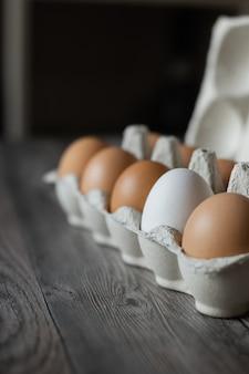 Коричневые куриные яйца и одно белое яйцо в коробке на деревянной поверхности.