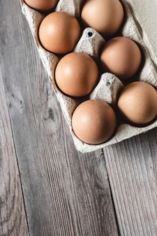 Brown chicken eggs in a carton on wooden surface. top view.