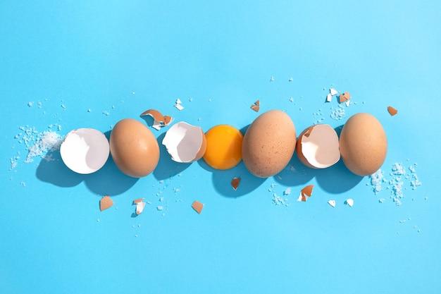 Коричневые куриные яйца, яичная скорлупа и яичный желток на синем фоне. плоская композиция.