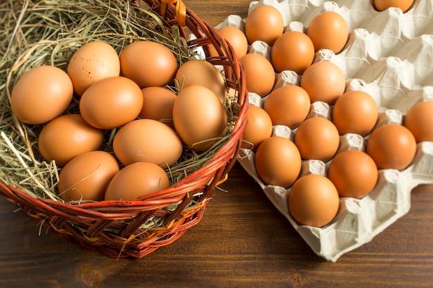 Коричневые куриные яйца в корзине и лотке для хранения